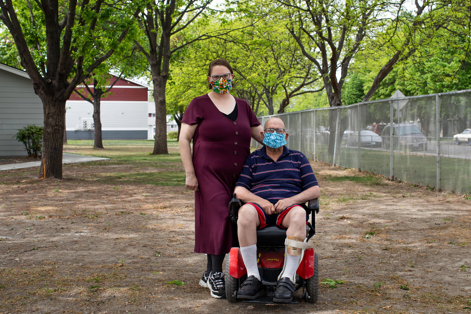 """Desirae Hernandez, a caregiver in Kennewick, Benton County, stands with her client Scott Philbeck, 60, at his apartment complex, April 29, 2020. """"It's been hard,"""" says Philbeck, looking to Hernandez for suppport with expressing how things have been lately. """"He doesn't get out much these days and the anxiety from that can be debilitating I've noticed. The masks create this additional layer of claustrophobic anxiety for my clients as well."""" (Matt M. McKnight/Crosscut)"""